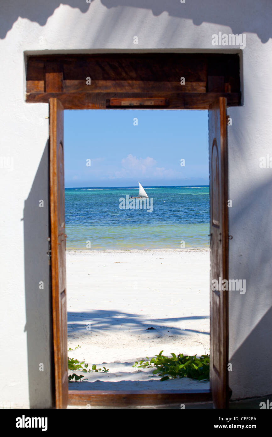 Looking through doorway at dhow, sailing in the sea off the coral reef at Bwejuu, Zanzibar Island, Tanzania Stock Photo