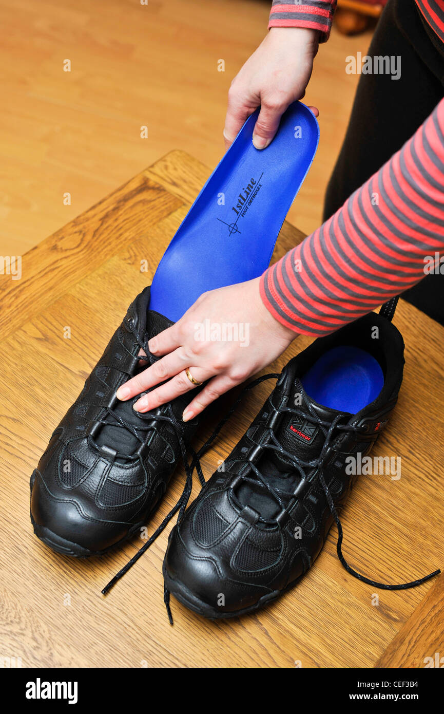 Inserting foot orthoses inner soles into shoes to help feet problem of badly formed arches - Stock Image