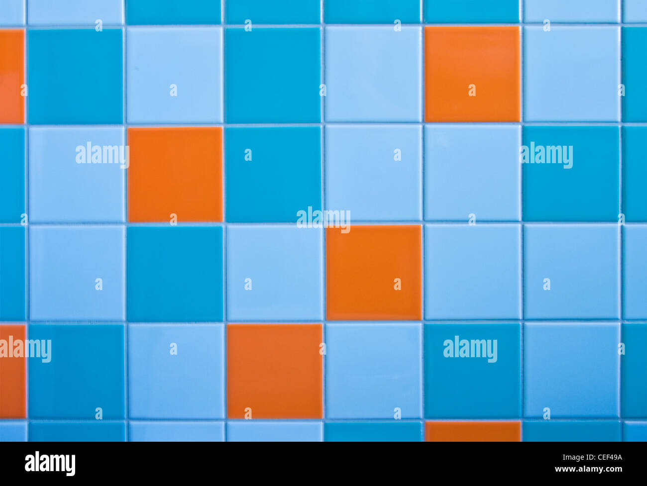 Part of wall in modern bathroom with tiles in light blue, azure blue and orange - Stock Image
