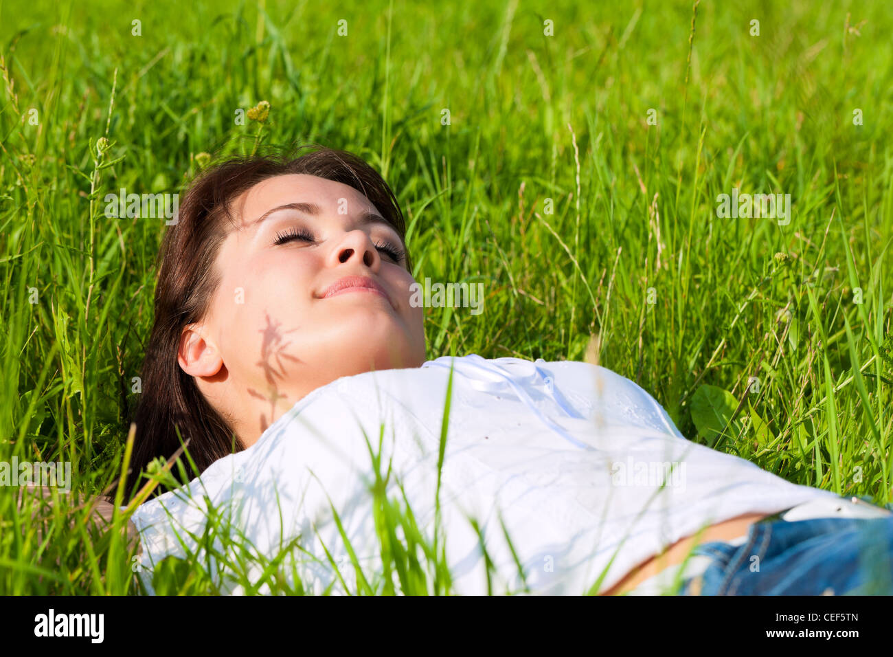Young woman laying on a lawn or meadow in summer and is dreaming or sleeping - Stock Image
