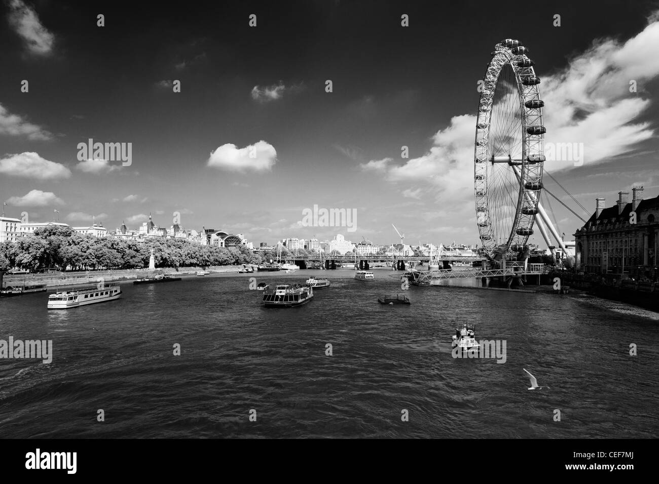 The London Eye with Charing Cross Station and Hungerford Bridge in the background, taken from the a boat on the - Stock Image