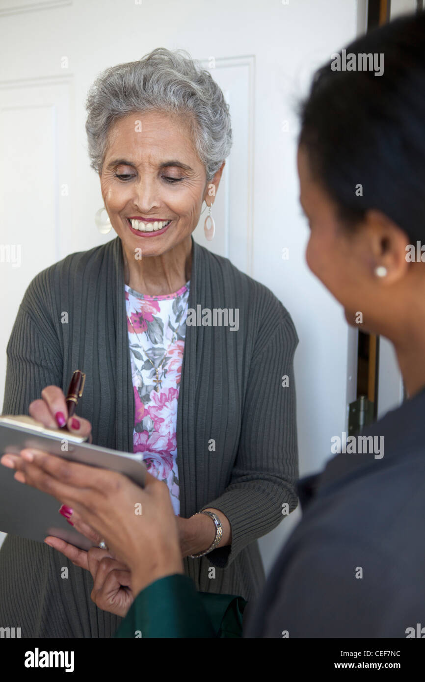 Black senior woman signs a petition at her front door - Stock Image