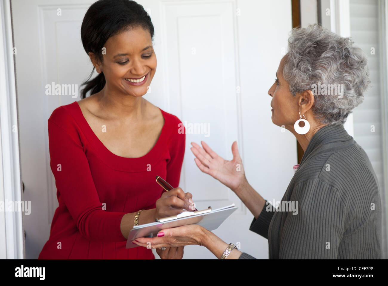 Black woman signs a petition at her front door - Stock Image