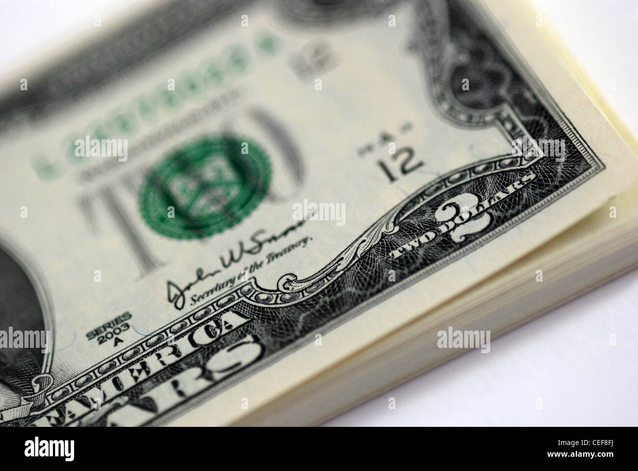 A close up of a stack of brand new usd two dollar bills.  On white background, shallow depth of field. - Stock Image