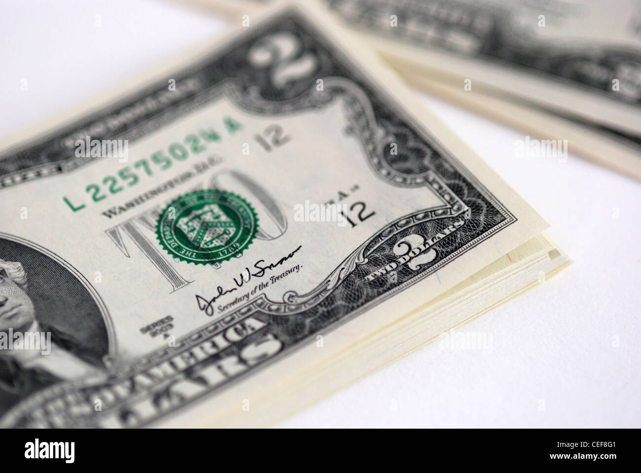 A stack of new USD two dollar bills, on white background - Stock Image