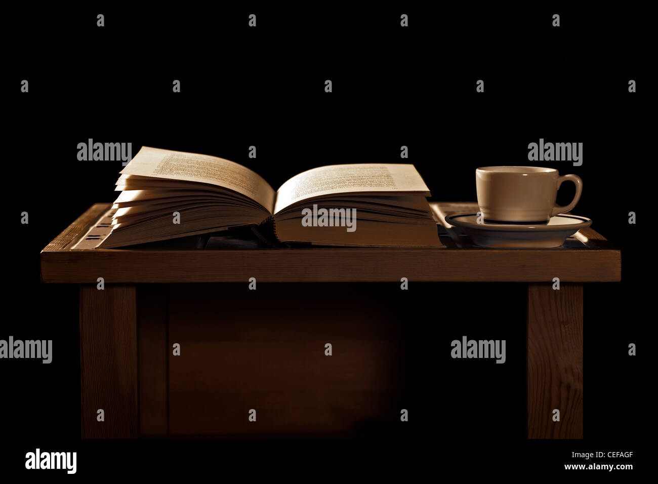 old wooden table with an open book and a cup of coffee - Stock Image