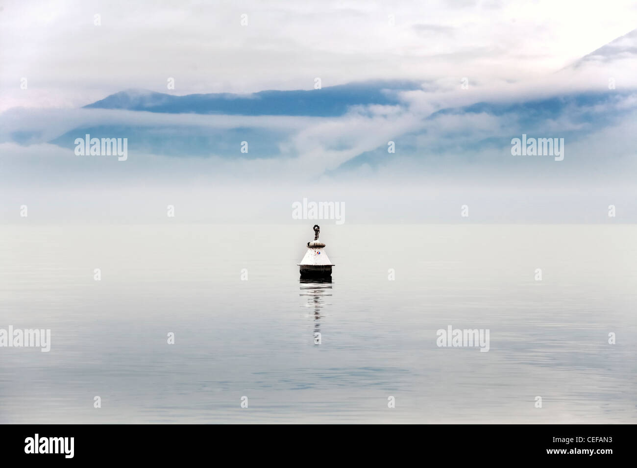 Buoy in fog and clouds on Lake Maggiore in the winter - Stock Image