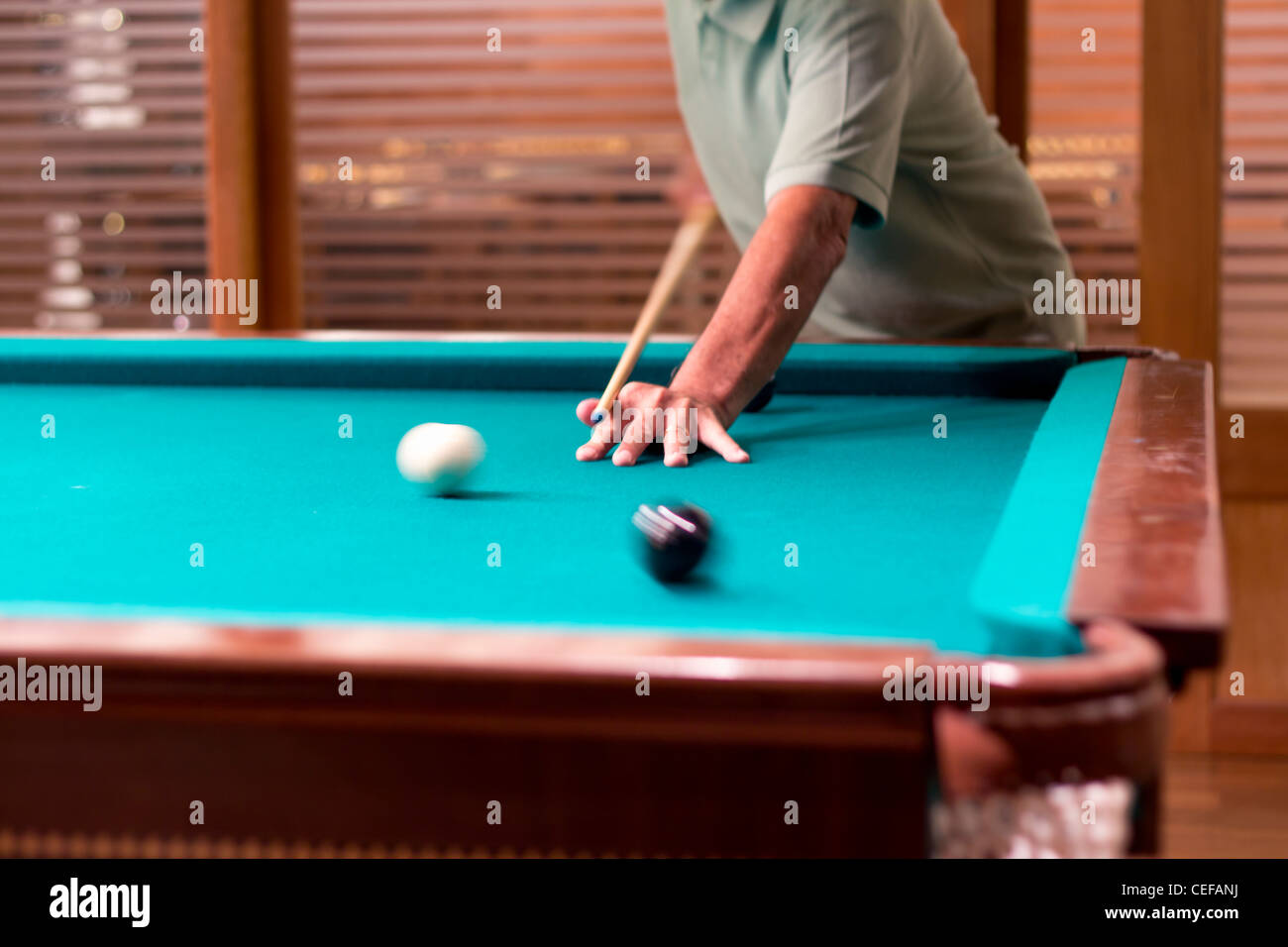 A man playing the last black ball of a snooker game. Motion effect on the balls. - Stock Image