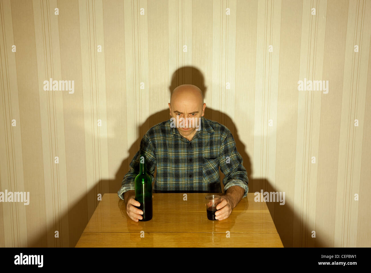 lonely drunken men sit the table with bottle - Stock Image