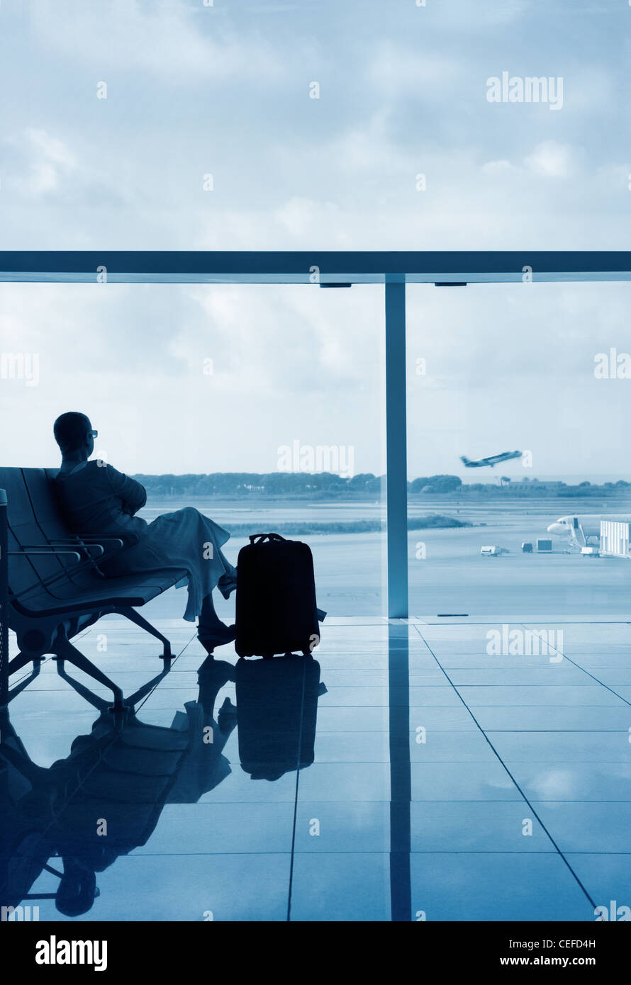 Lady in a lobby airport waiting for her flight, looking through a glass with solar protection. Stock Photo
