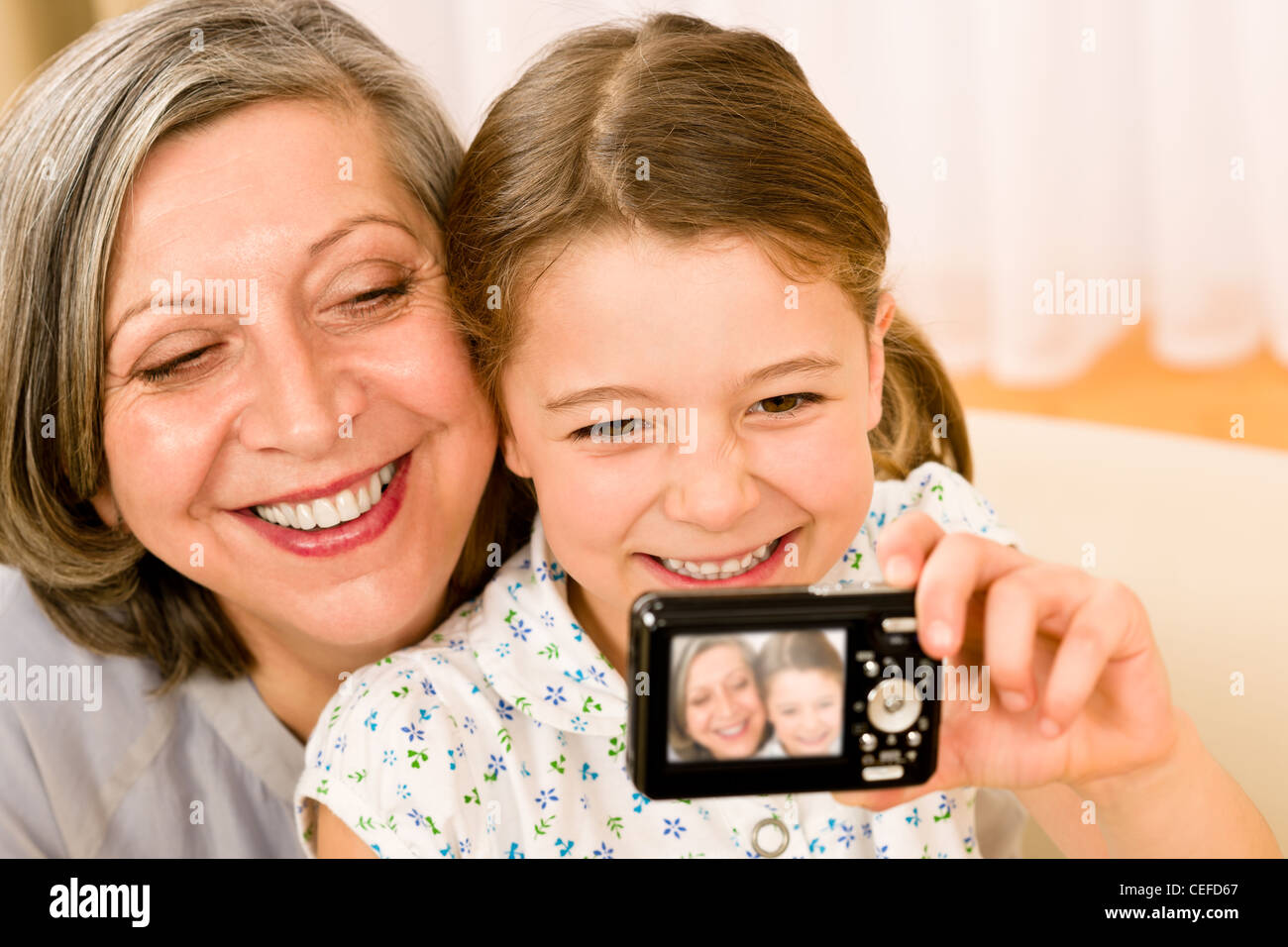 Grandmother and granddaughter take picture themselves smiling close-up portrait - Stock Image