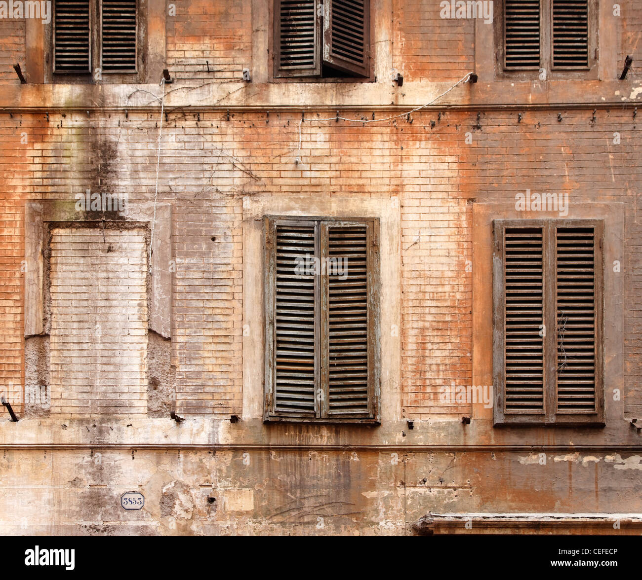 Wooden shutters on abandoned building - Stock Image