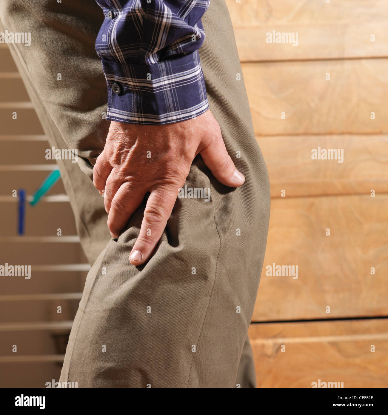 Older man rubbing back of his knee - Stock Image