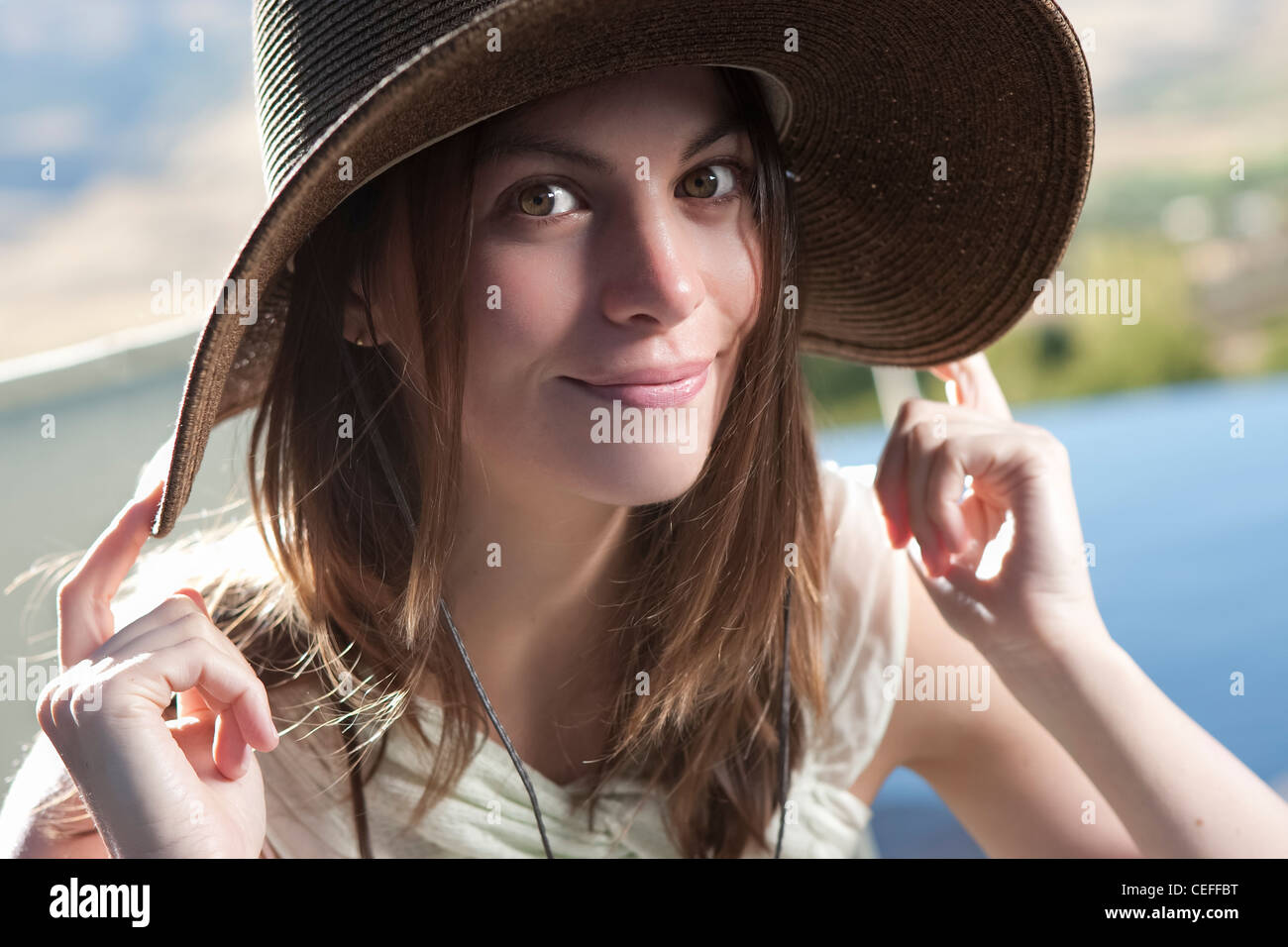 Smiling woman wearing hat outdoors - Stock Image