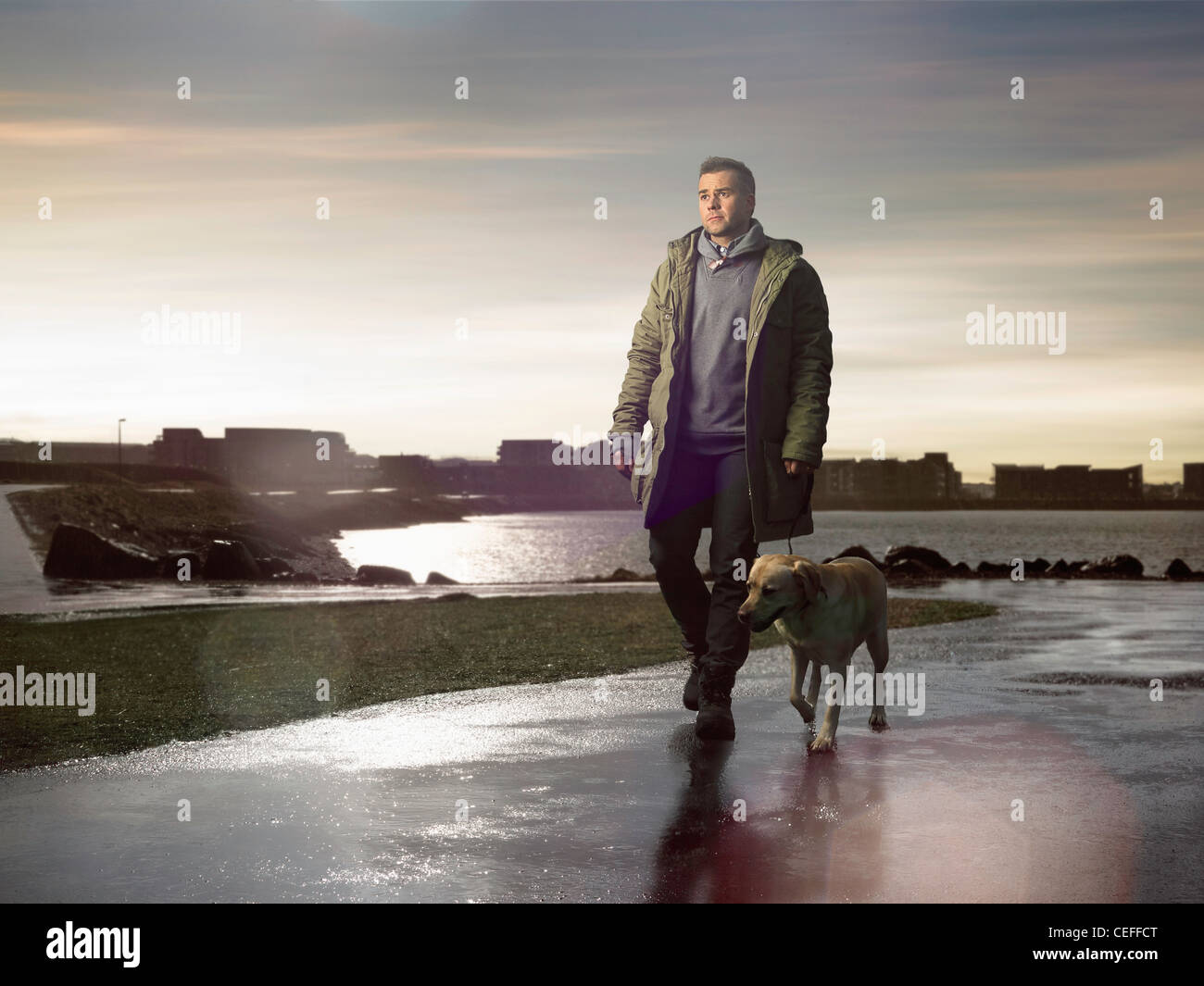Man walking dog on wet road - Stock Image