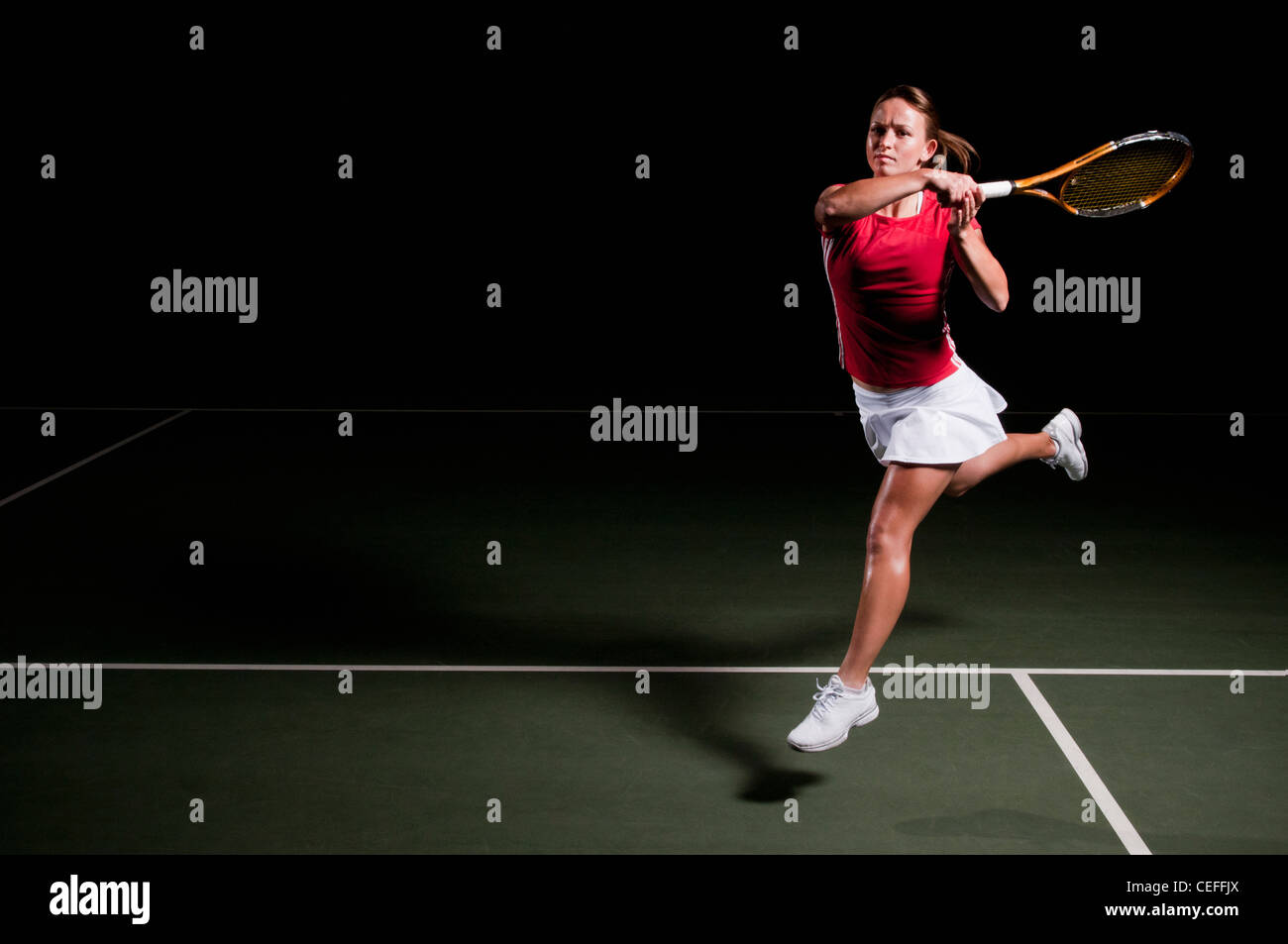 Woman playing tennis indoors - Stock Image