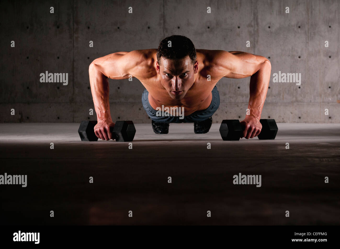 Athlete doing push ups on weights Stock Photo