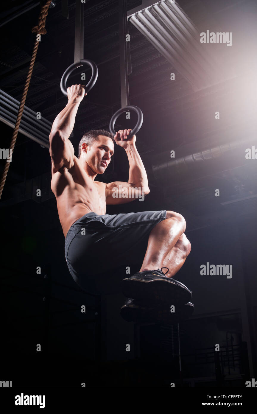 Man using suspended rings in gym - Stock Image