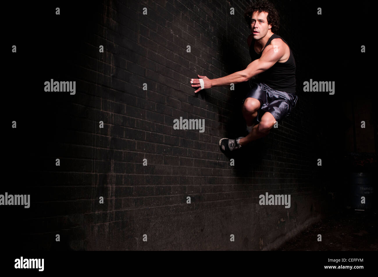 Runner bouncing off side of wall Stock Photo