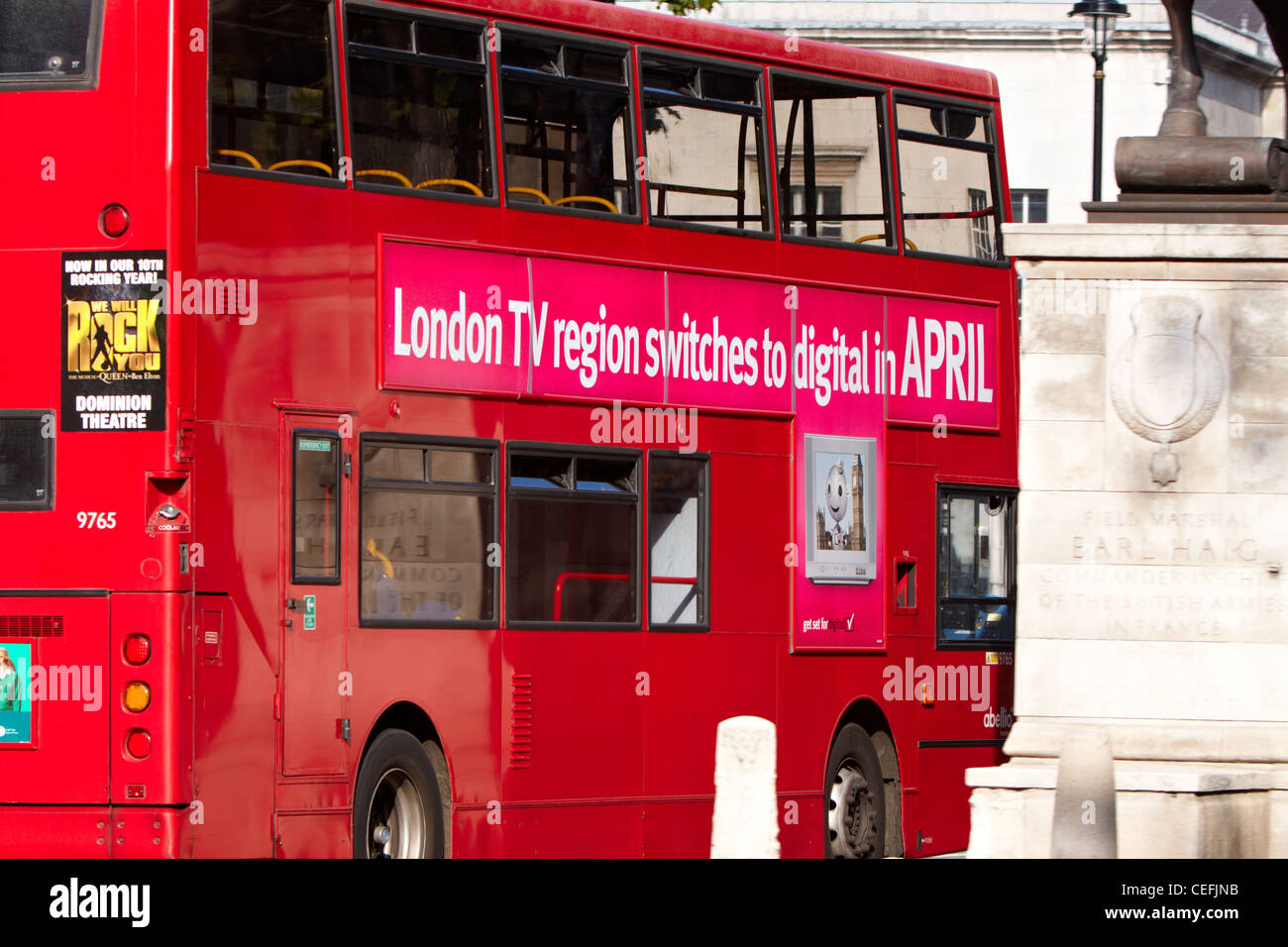 Red double decker bus advertising London digital TV switchover - Stock Image