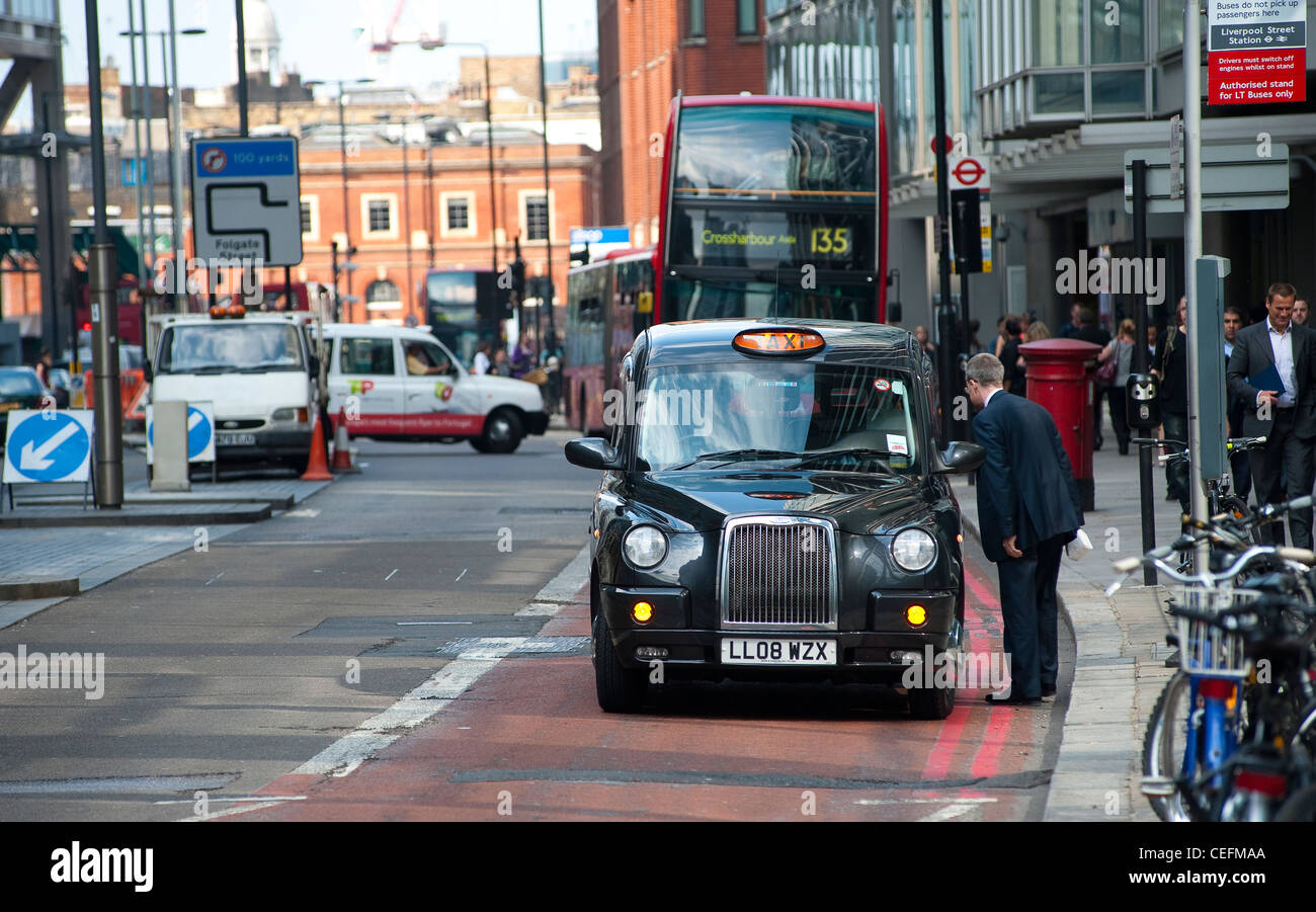 Black taxi cabin London picking up a fare. - Stock Image