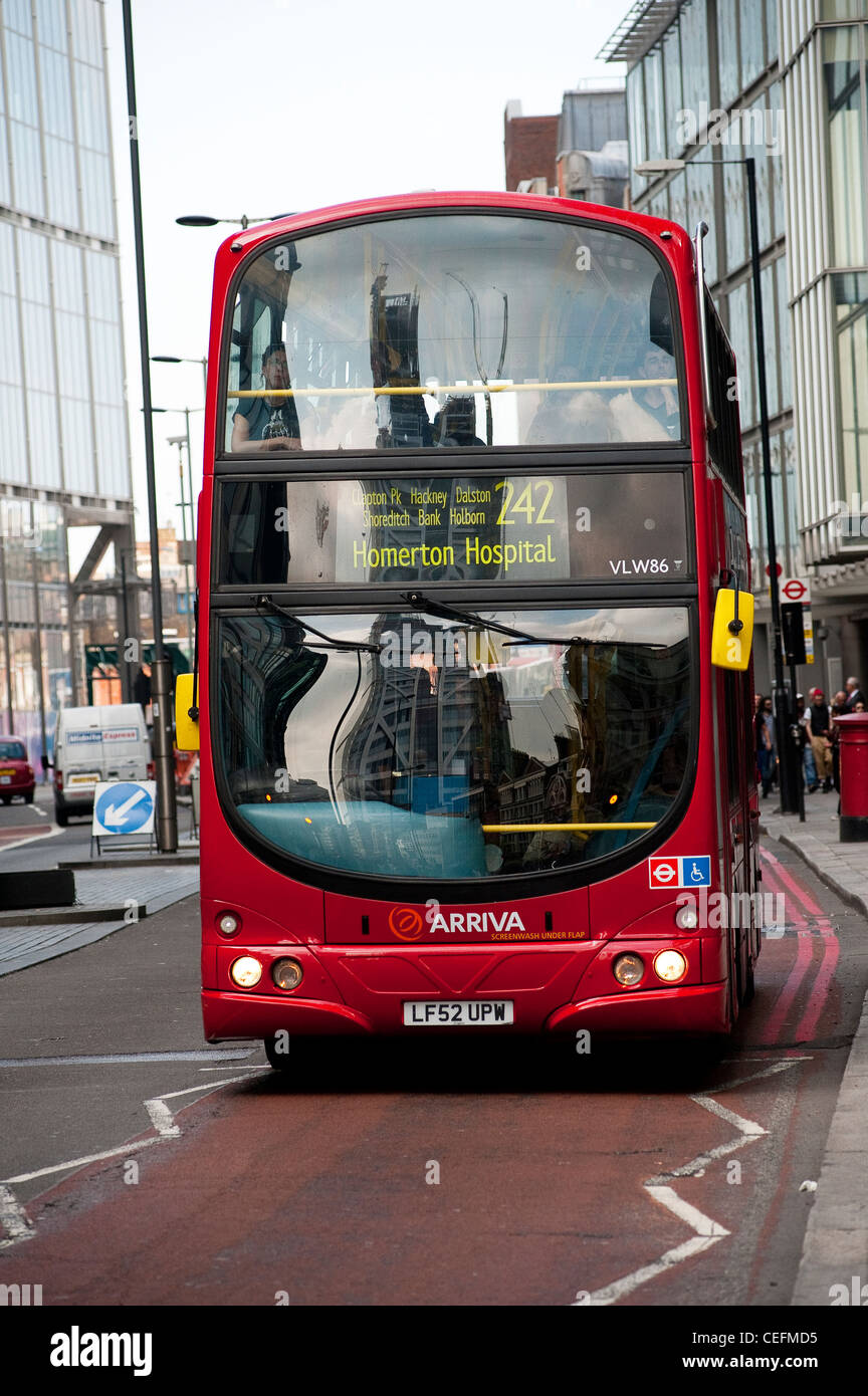 Red double decker bus driving along a bus lane on a street in the city of London, England. - Stock Image