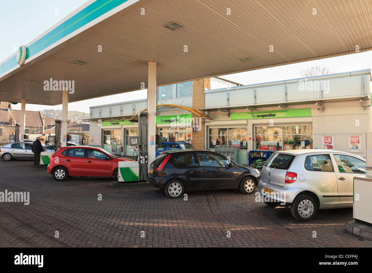 BP filling station forecourt with cars at the petrol pumps. North Wales UK Britain. - Stock Image