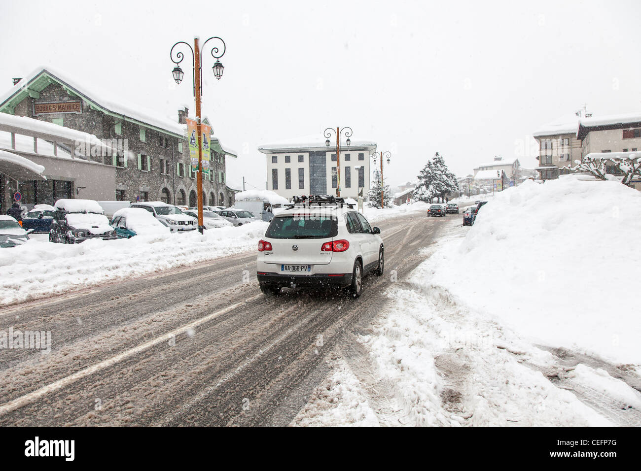 Cars driving along a road in bad snowing weather conditions, Bourg St Maurice, France - Stock Image