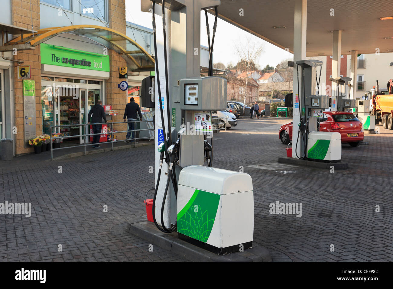 Fuel pumps on a BP filling station forecourt with Co-operative shop convenience store. UK Britain - Stock Image