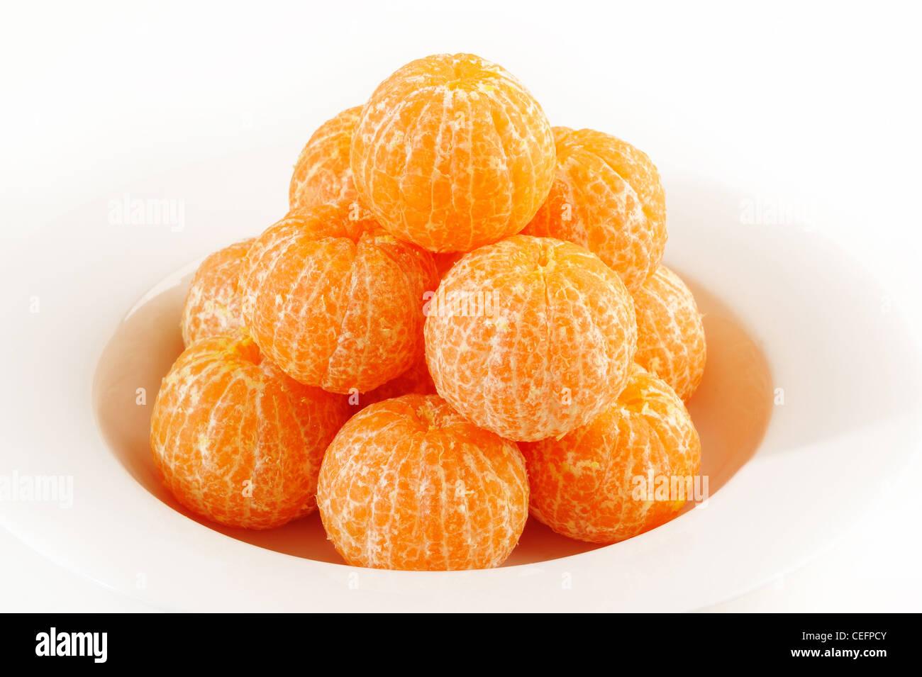 Mandarin orange on white dish - Stock Image