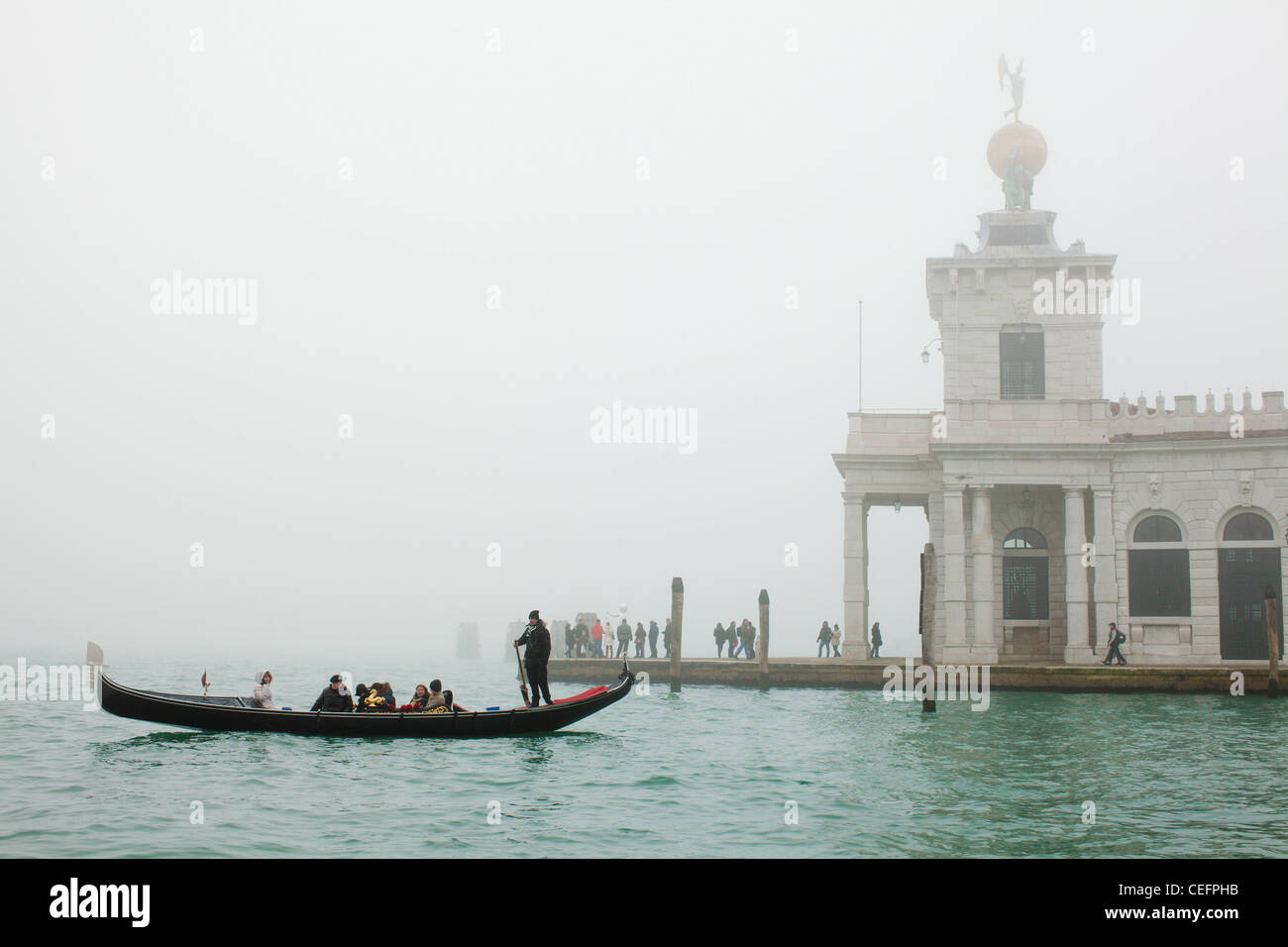 A gondola crosses the Bacino di San Marco in heavy fog in front of the Punta della Dogana. Venice, Italy. - Stock Image