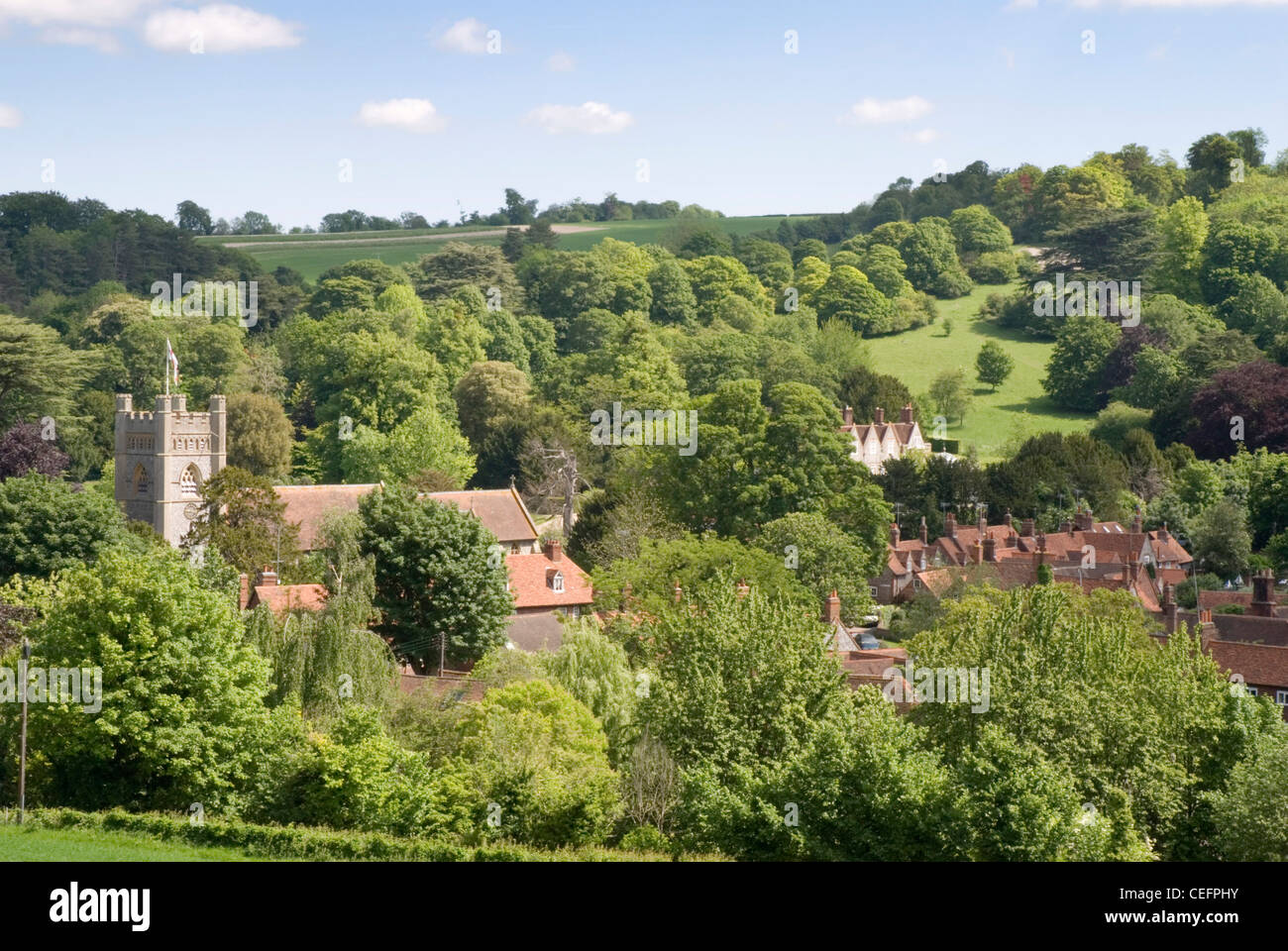 Chiltern Hills -view over sunlit  Hambleden village - Bucks - wooded hills - trees in early summer leaf - Stock Image
