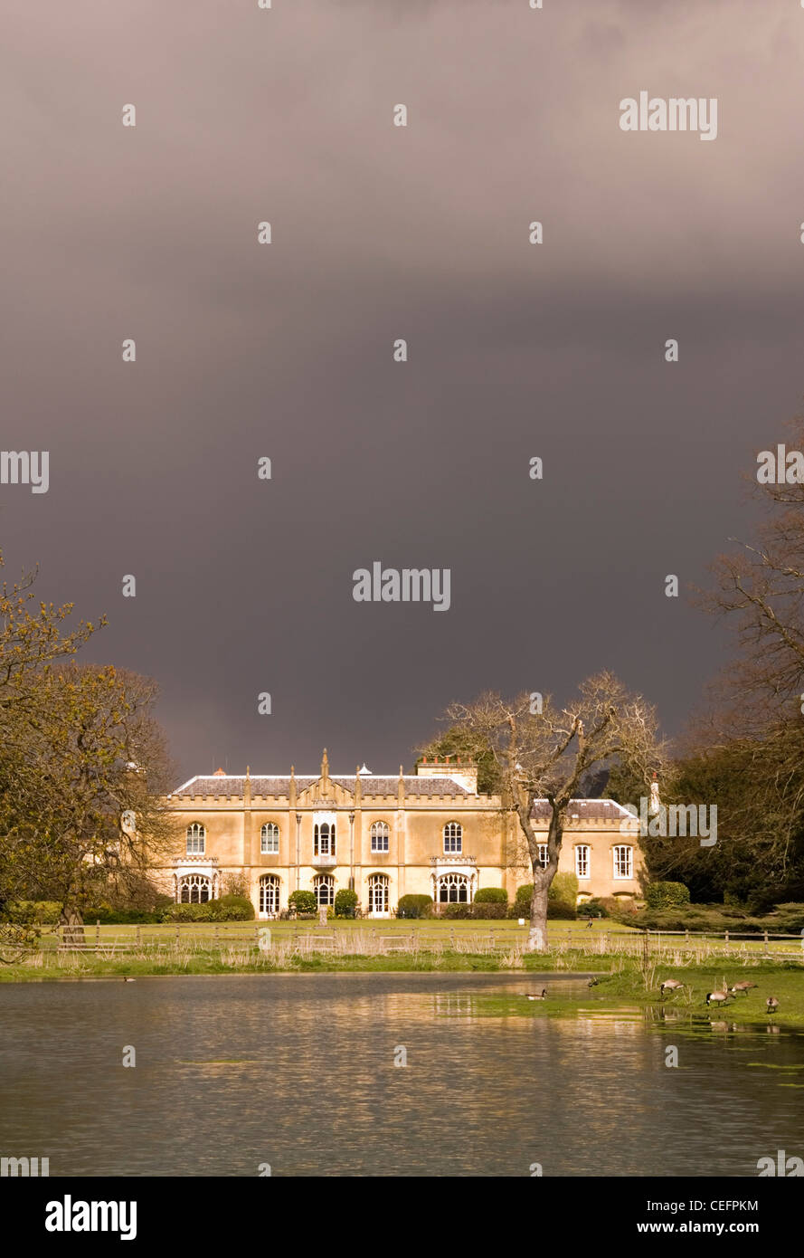 Great Missenden - Missenden Abbey - sun lit beneath storm clouds - reflected in a lake - Stock Image