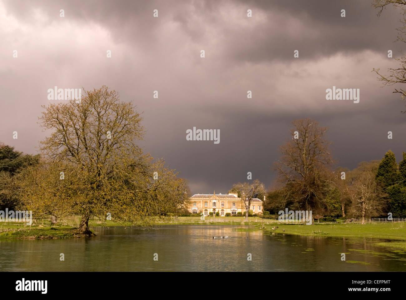 Great Missenden - Bucks - Missenden Abbey - seen across a lake - sunlight -  storm clouds approaching - Stock Image