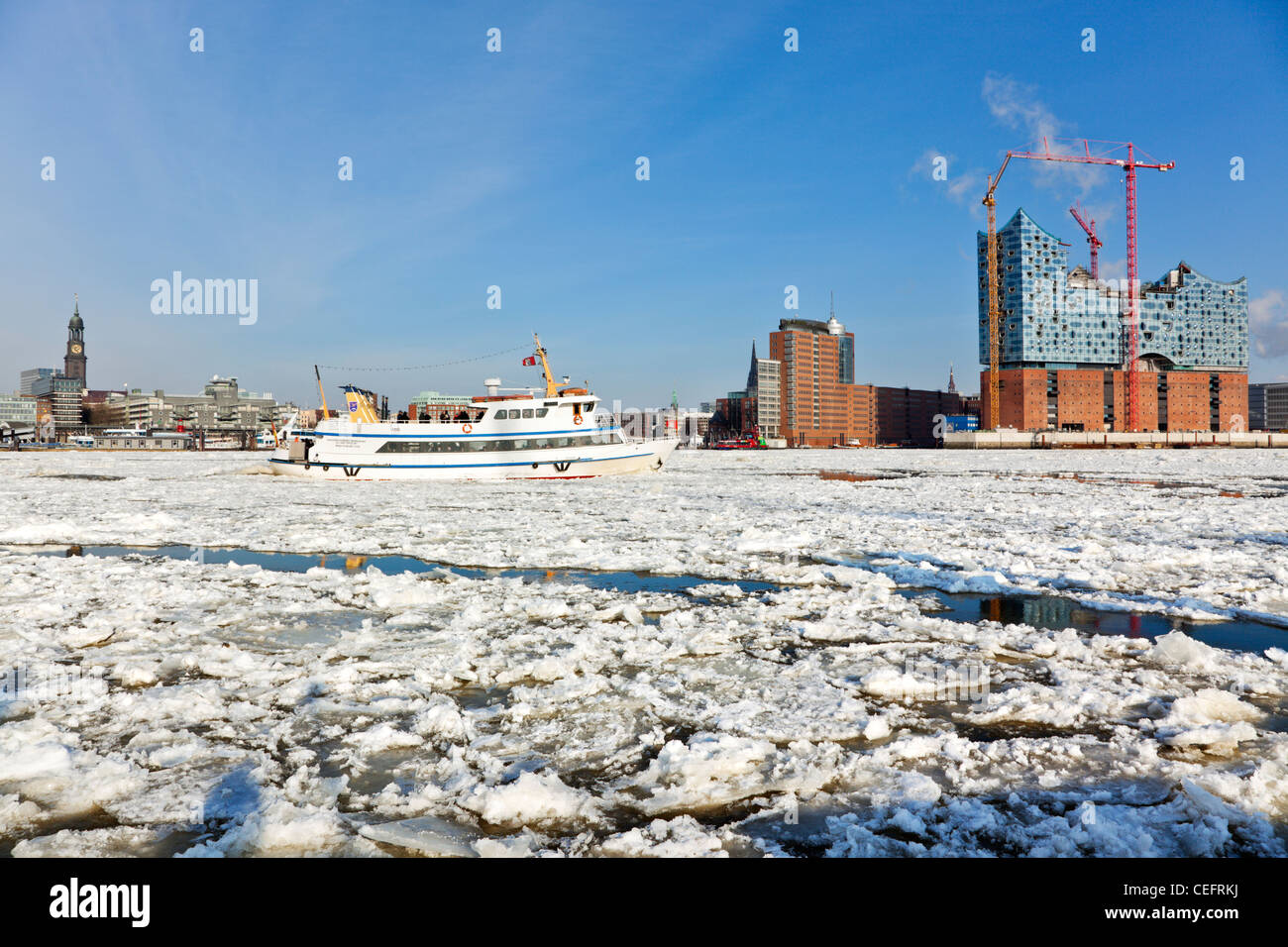Hamburg and the frozen Elbe river from Saint Michaels church to the Elbphilharmonie construction site, tourist boat - Stock Image