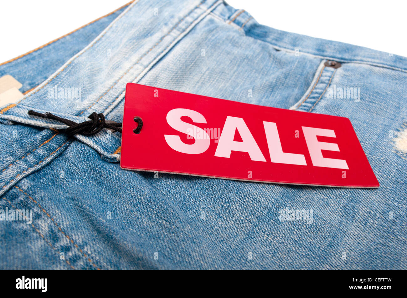 Closeup of Blue Jeans With Red Sale Tag - Stock Image