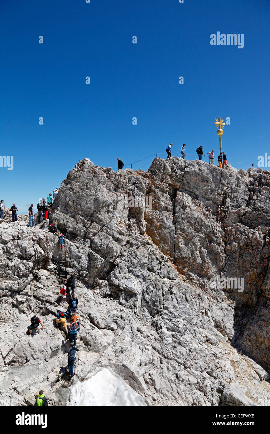 Tourists climbing to the Golden Cross - the highest point in Germany on the summit of Zugspitze at 2,962 m above - Stock Image