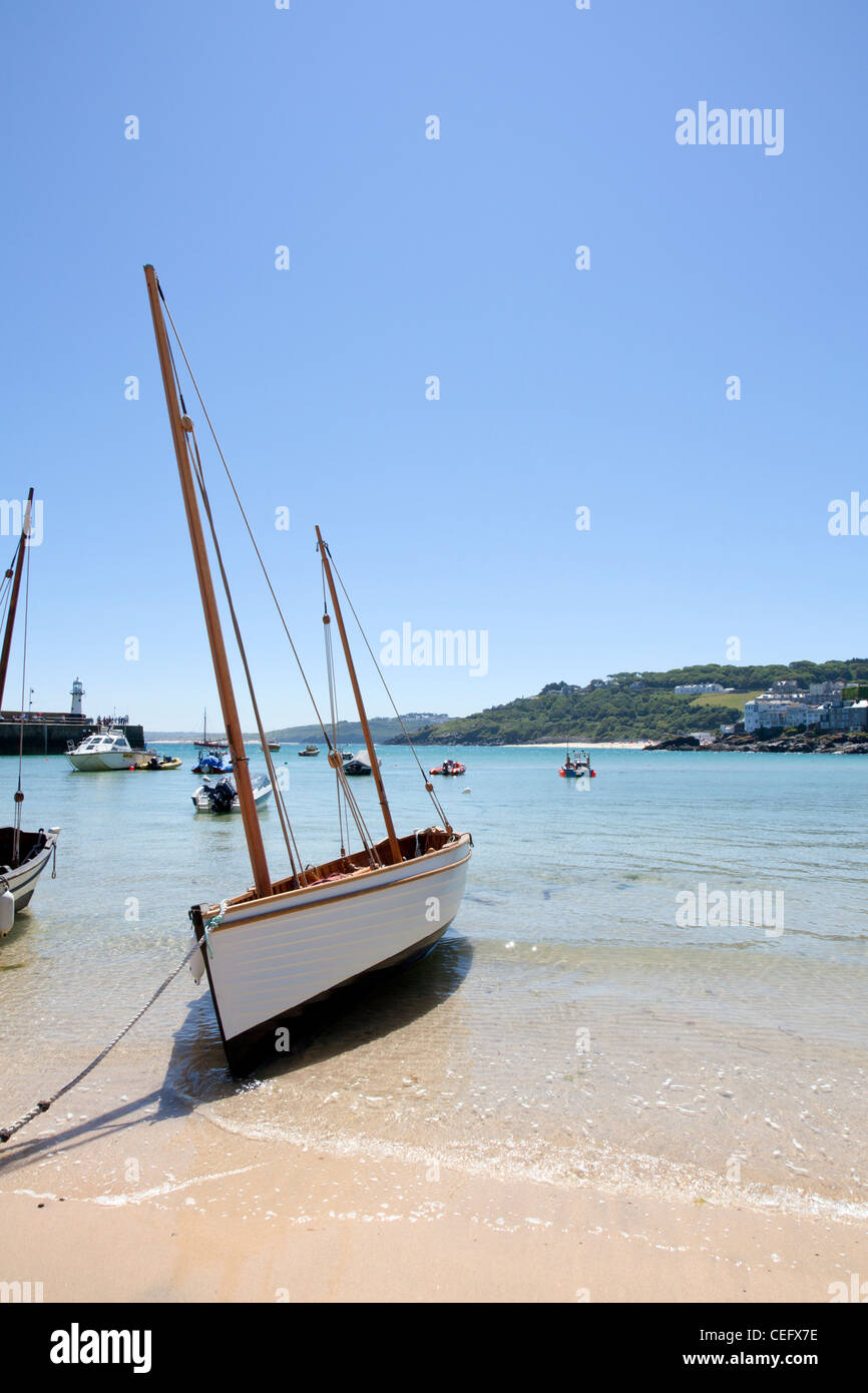 St Ives, Cornwall, England sail boat on coastline on sand beached in harbour harbor - Stock Image