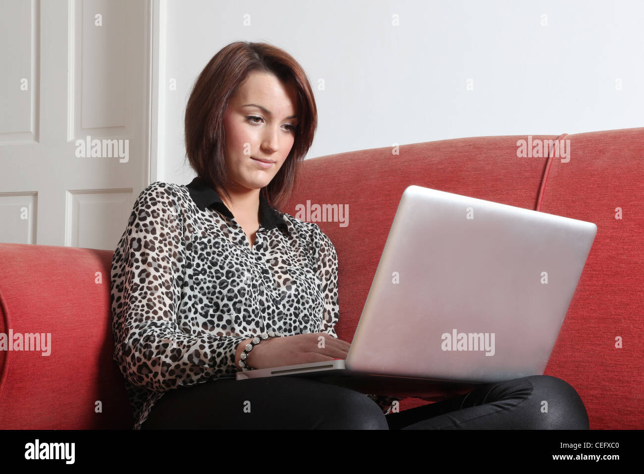 Profile of a single young female using a laptop. - Stock Image