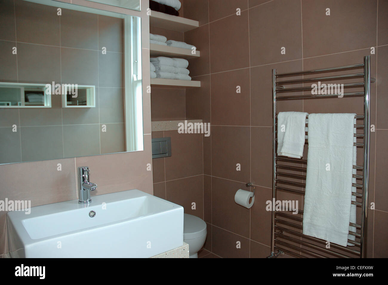 ee8842789aae5 Large mirror above rectangular white basin in modern brown bathroom ...
