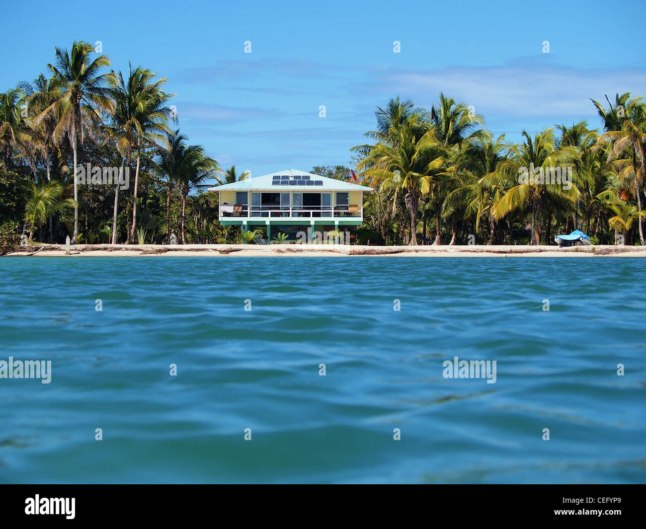 Tropical off grid beach house with solar panels seen from the sea - Stock Image