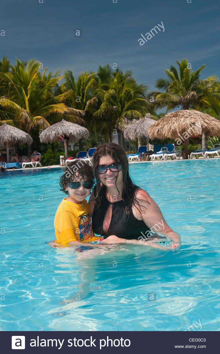 Single mother enjoying a holiday with her son in a tropical country. Bathing in a pool and having fun - Stock Image