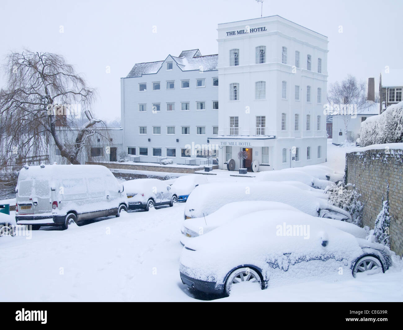 Snow-covered parked cars in front of the Mill Hotel building in Sudbury, Suffolk, England. - Stock Image