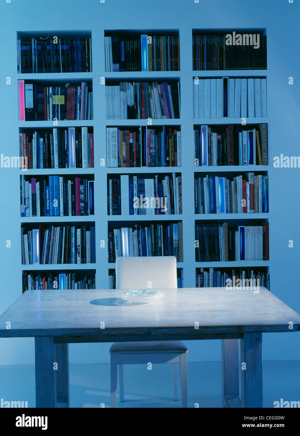 White table and chair in front of recessed bookshelves in modern dining room - Stock Image