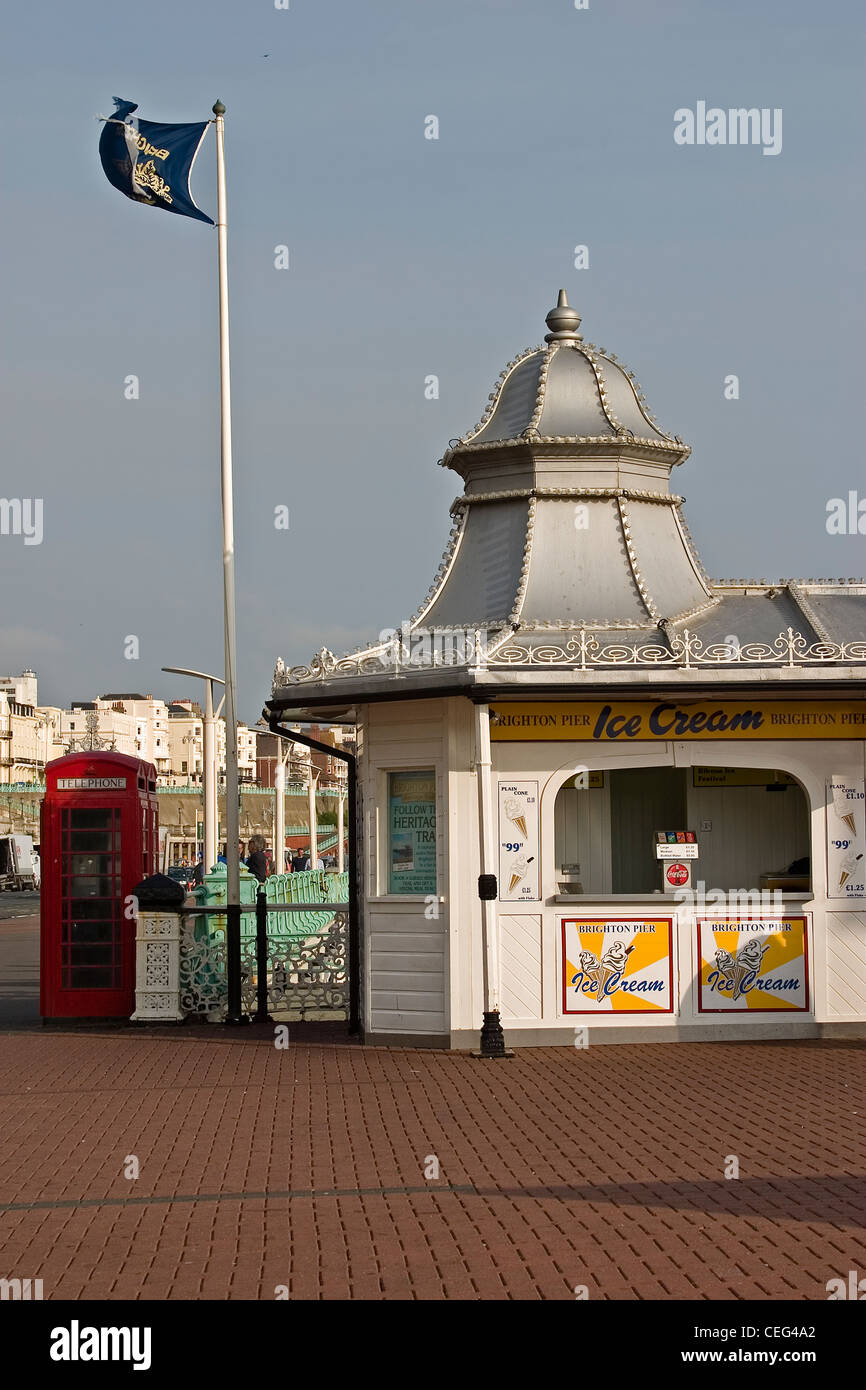 Brighton pier ice cream kiosk flag and red telephone box - Stock Image