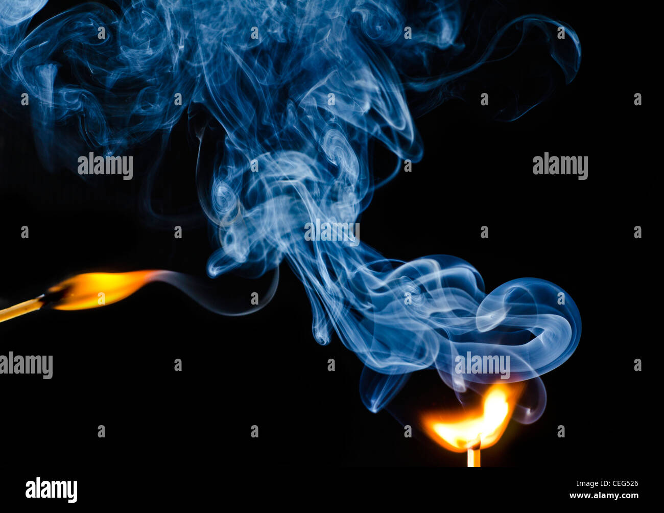 Striking of a match showing smoke rising against a black background. Stock Photo
