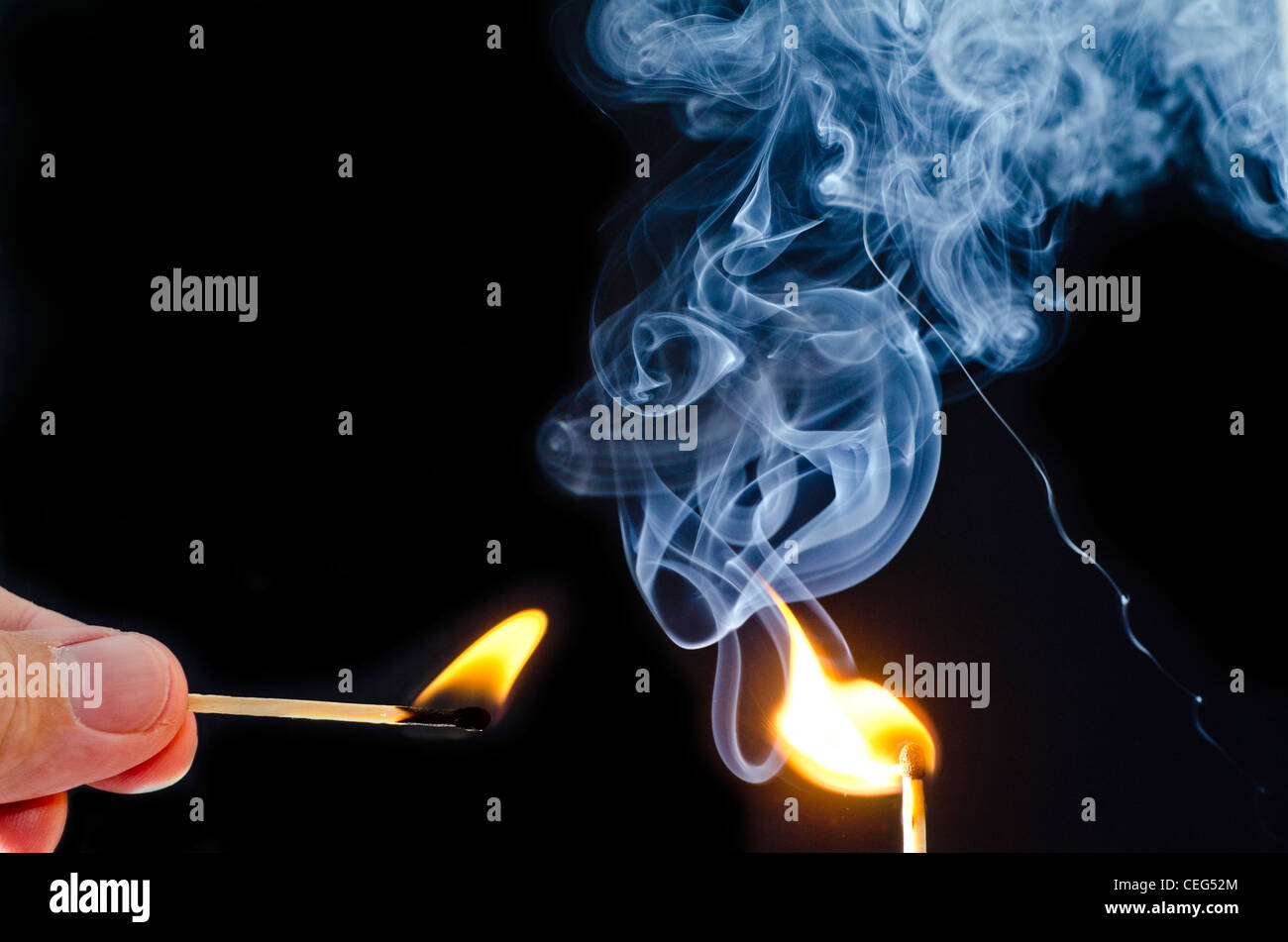 Man lighting a match with another match, with blue smoke rising against a black background. Stock Photo