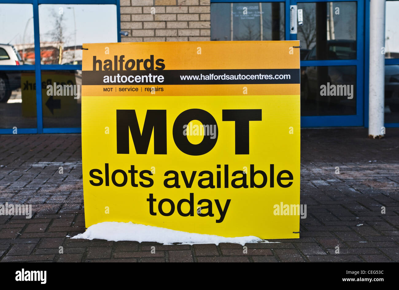 A Halfords 'MOT slots available today' sign, UK - Stock Image