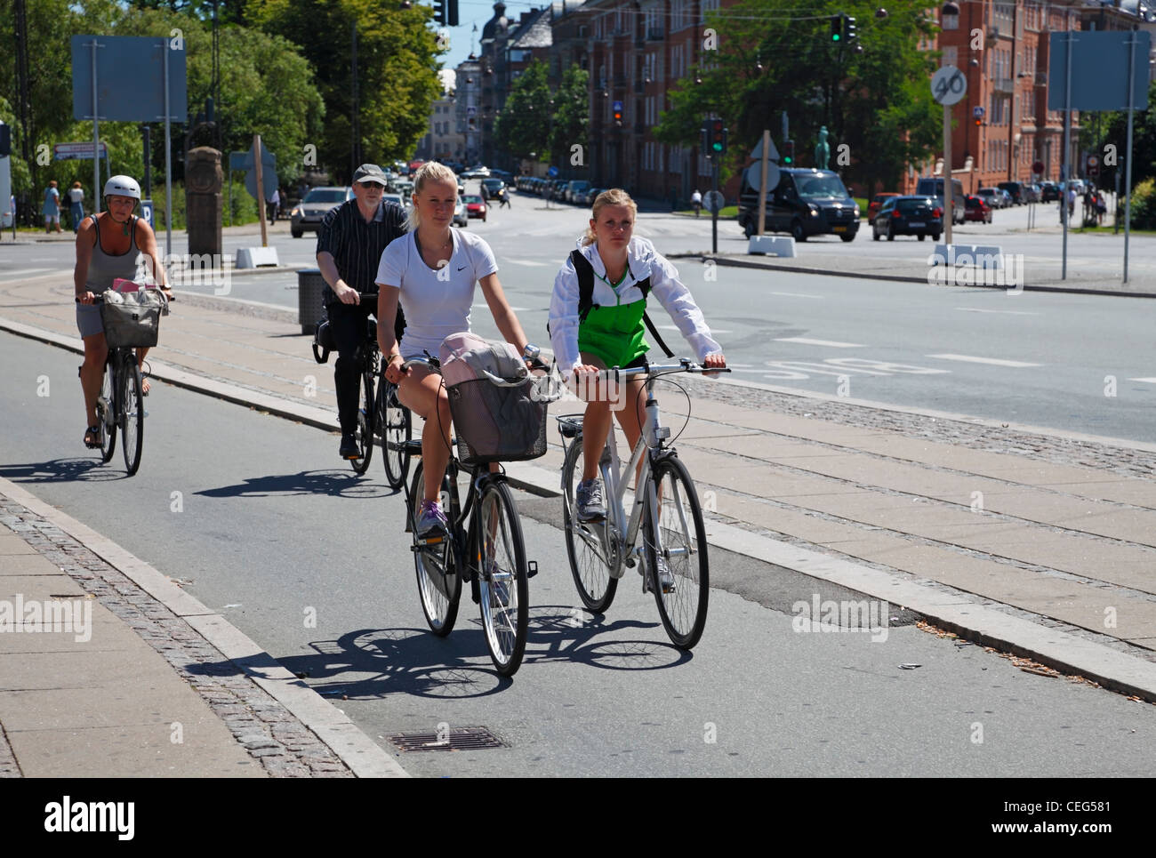 Girls cycling in Copenhagen, Denmark, on one of the many bicycle lanes along the streets - at Østerport Station, Stock Photo