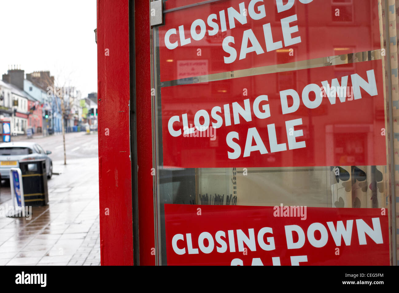 closing down sale signs in a small high street business window in the uk falling sales in british high st shops - Stock Image